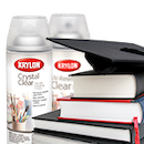 Krylon spray paint cans behind a stack of textbooks and a graduation mortar board hat